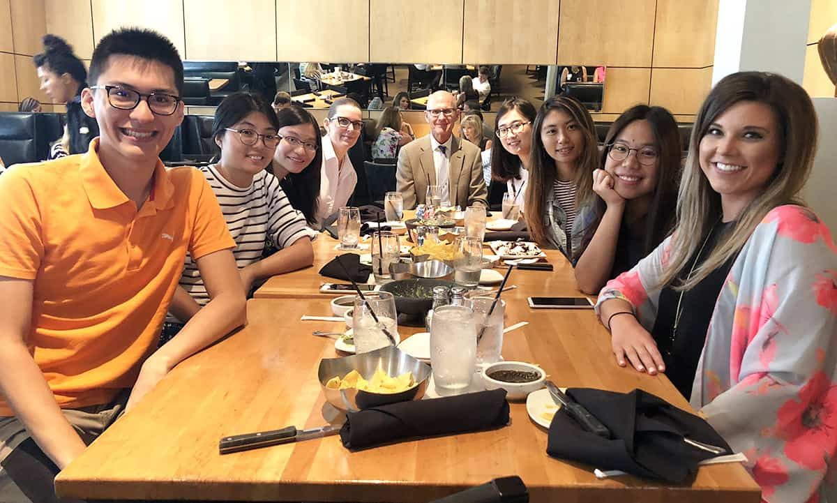 Dean Keith Olsen, Pharm.D., center, gets ready to share a meal with the six students from Kaohsiung Medical University in this year's exchange and guests.