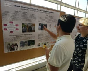 Researchers talking near poster