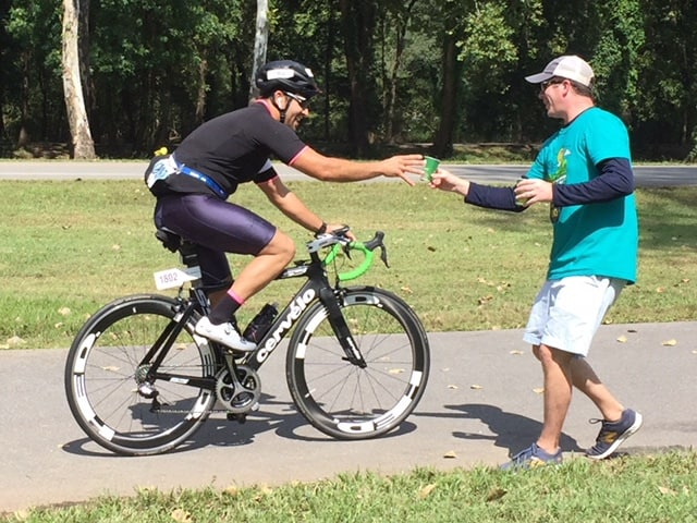 Volunteer Blake Pond with the Myeloma Center shares water and Gatorade with riders at the center's aid station in Burns Park during the 2018 Ride for Research on Sept. 29.