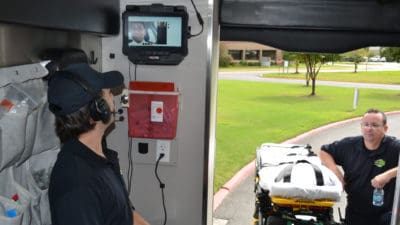 Sanjeeva Onteddu, M.D., center on the video monitor, works with ProMed Ambulance Service paramedics to demonstrate how the live video telemedicine system installed in the ambulance will work in the field.