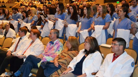 UAMS College of Nursing juniors stand and recite the Nightingale Pledge before putting on their white coats on stage.