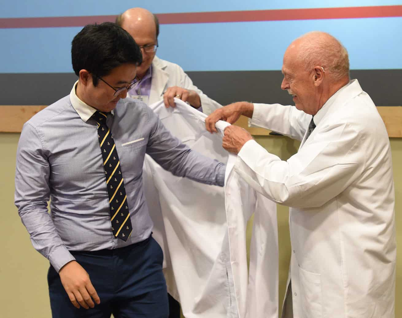 Student helped into white coat