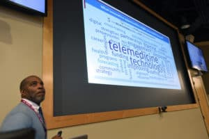 Mario Wallace of Organizational Development looks as employees' answers to questions are shown on the screen during the town hall meeting.