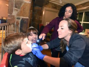 Ashley McMillan, D.D.S., examines a trick-or-treater's teeth during Boo at the Zoo. Jennifer Stane and the Delta Dental Tooth Fairy look on.