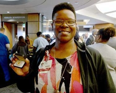 Kristy Caldwell holds up her pin recognizing her 15 years of employment and service at UAMS.