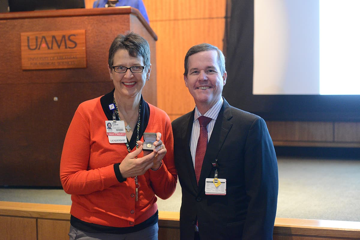 UAMS Chancellor Cam Patterson, M.D., MBA, and Mary Cantrell stop for a photo at the Employee Services Awards ceremony.