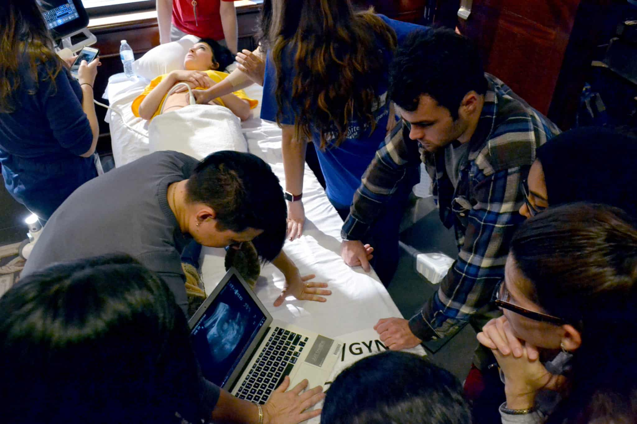 UAMS faculty work as volunteer instructors demonstrating ultrasound applications on a college student volunteer as medical students observe and learn during Ultrafest.