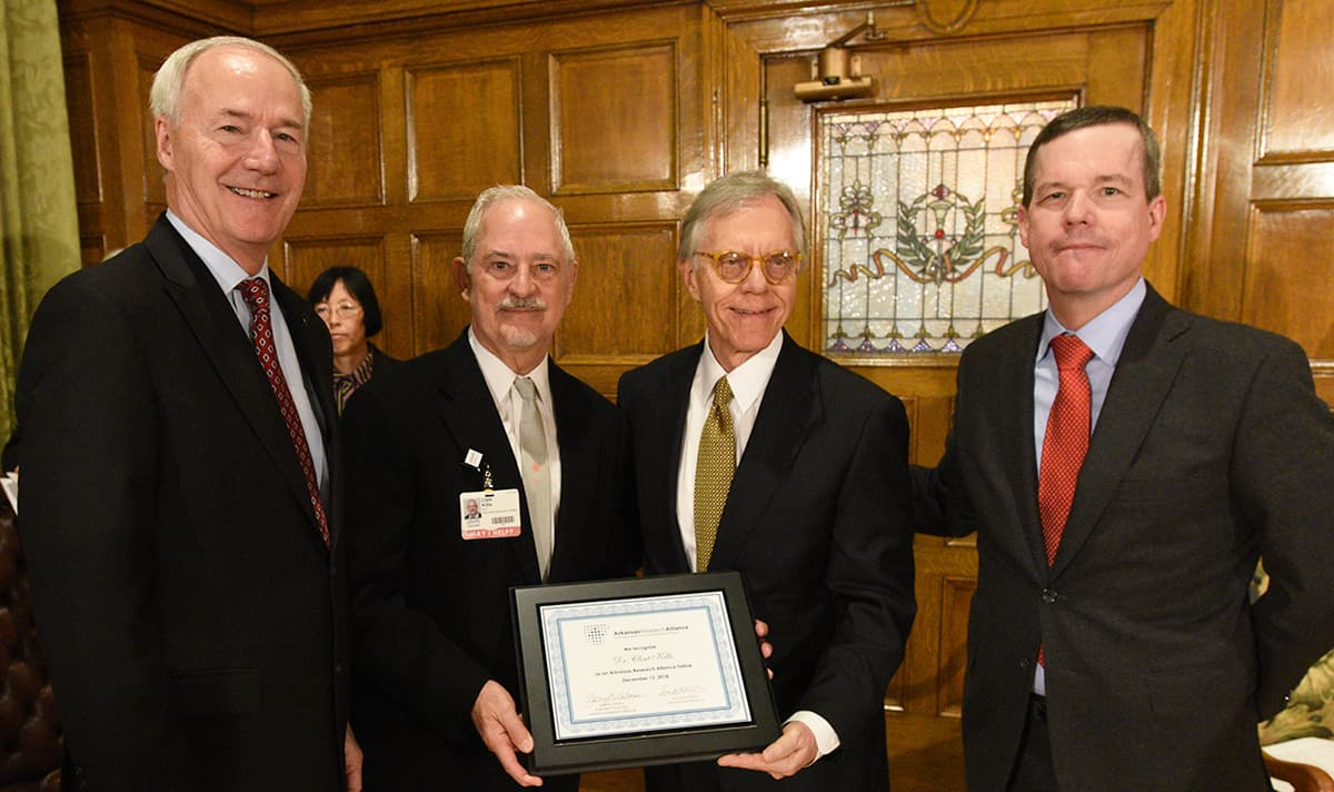 UAMS researcher Clint Kilts, Ph.D., second from left, receives a certificate naming him an Arkansas Research Alliance Fellow. Gov. Asa Hutchinson, left, ARA CEO Jerry Adams, third from left, and UAMS Chancellor Cam Patterson congratulate Kilts on receiving the honor.