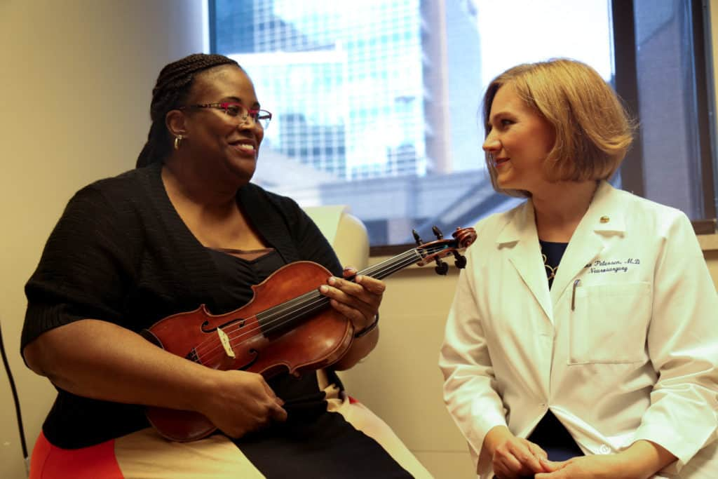 Woman holding violin next to doctor