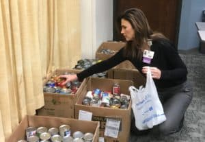 Tonya Johnson helps sort canned goods that were donated during the employee celebrations.