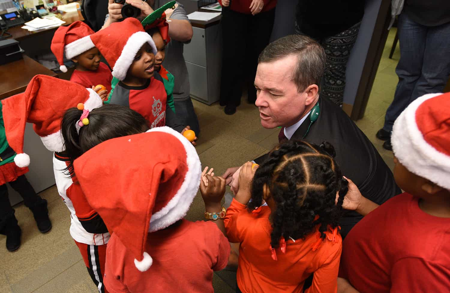 UAMS Chancellor Cam Patterson greets students from Head Start Sherwood, who came to carol on campus.