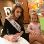 Miss Arkansas 2018 Claudia Raffo signs an autograph for a fan. Raffo and four former Miss Arkansas titleholders were special guests at the UAMS Alumni Association holiday open house.