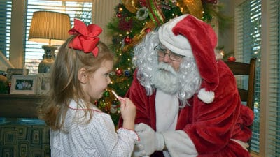 James Pruss as Santa Claus listening to Christmas wishes.
