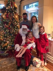 James Pruss, as Santa, enjoys a holiday gathering with Theresa Wyrick, M.D. and her family.
