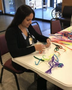 Melissa Stueben, with the UAMS College of Health Professions, volunteers at a craft station set up for kids as they await eye exams.