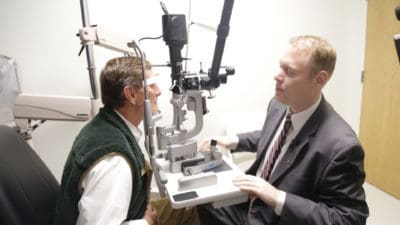David Warner gives Whit Hall an eye exam after having done a successful cornea transplant.