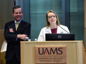 Paula McClain, a first-year student in the College of Medicine, speaks to the Board of Trustees as Chancellor Cam Patterson looks on.