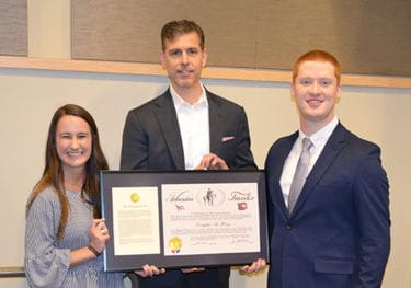 The student chapter presented Hoey, center, with an Arkansas Traveler certificate in thanks for his visit to UAMS.