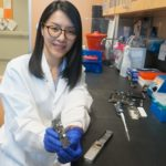 Thidathip (Tip) Wongsurawat, Ph.D., with the hand-held nanopore device used for the first time to sequence multiple viruses.
