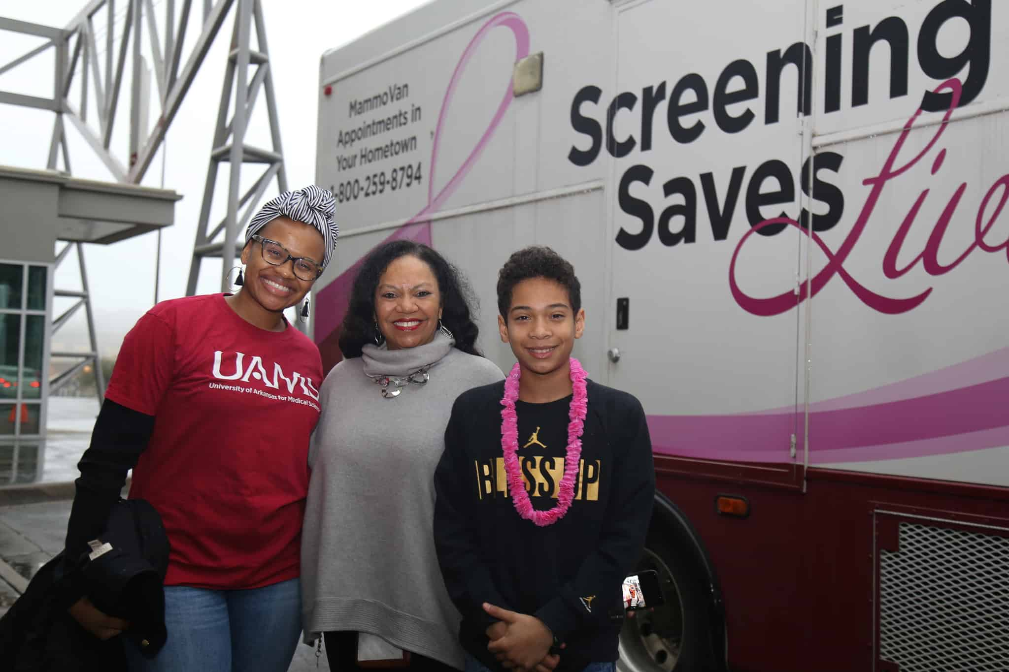 Expo volunteers (from left) Margaret Woods, Ronda Henry-Tillman, M.D., and her son Anders Tillman in front of the UAMS MammoVan.