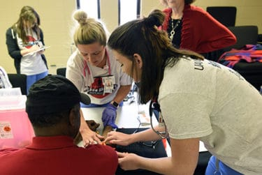 Student volunteers at the event draw blood from one of the attendees for a health screening.