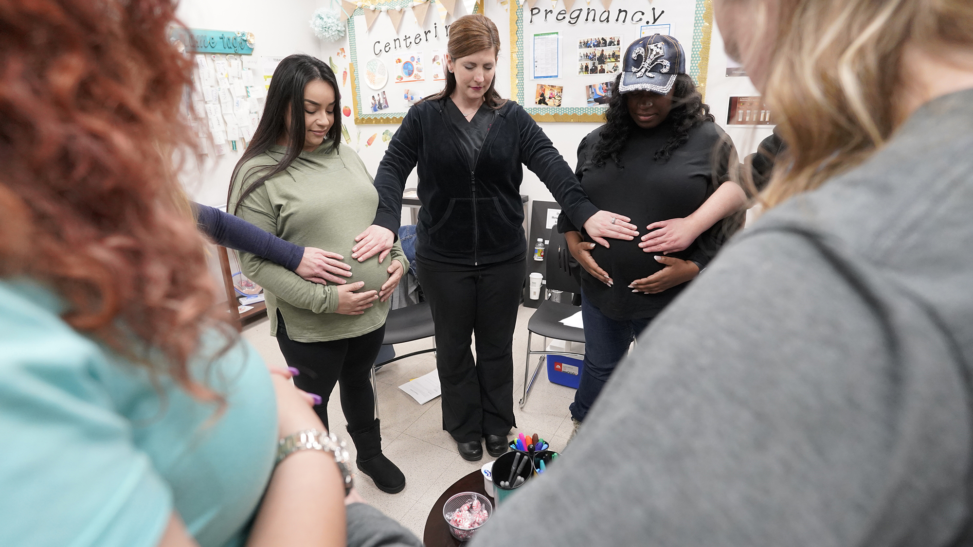 Pregnant women in circle touching bellies