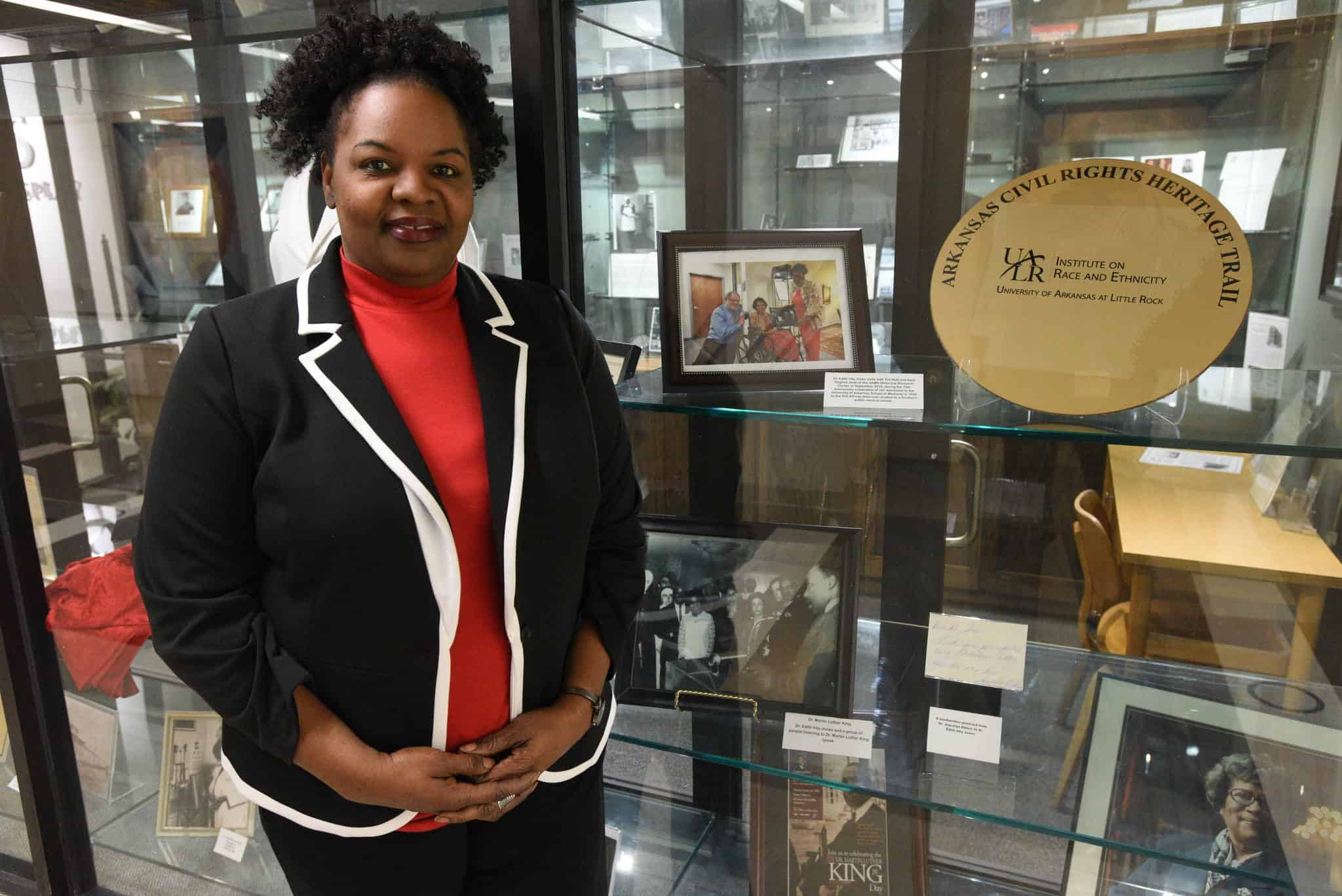 April Hughes standing next to her favorite elements in the exhibit, including a photo taken with Edith Irby Jones and a photo of Jones meeting Martin Luther King, Jr.