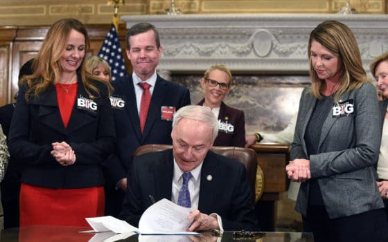 (From left) Arkansas Sen. Missy Irvin; UAMS Chancellor Cam Patterson, M.D., MBA; and Rep. Michelle Gray look on as Gov. Asa Hutchinson (seated) signs Senate Bill 151 in support of the UAMS Cancer Institute's quest for National Cancer Institute Designation.