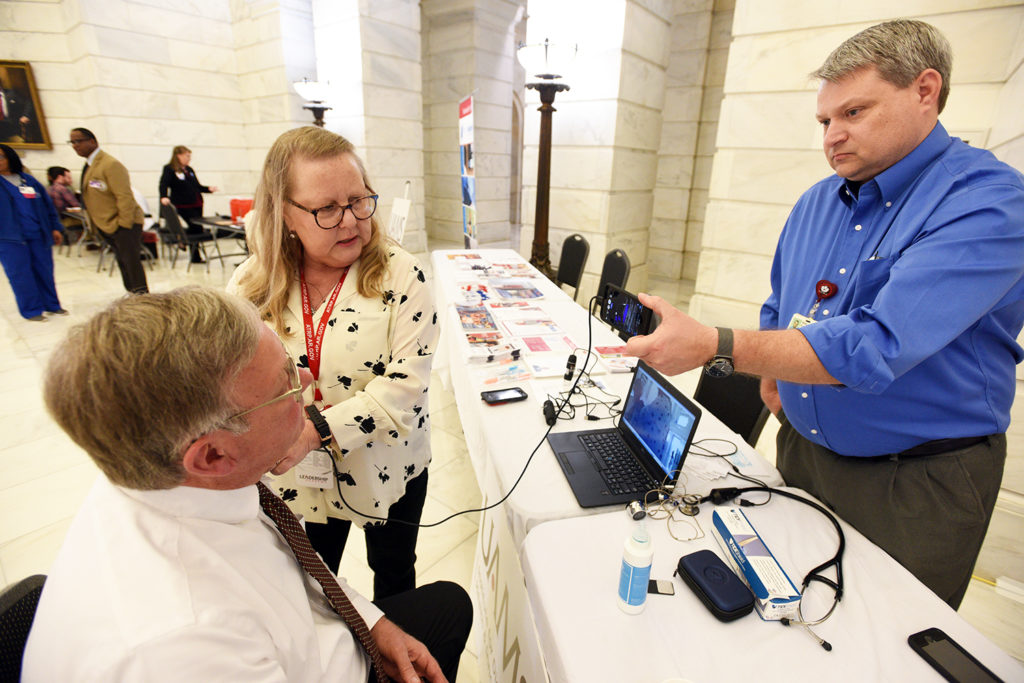 Representatives from the UAMS Institute for Digital Health & Innovation demonstrate a handheld ultrasound device.