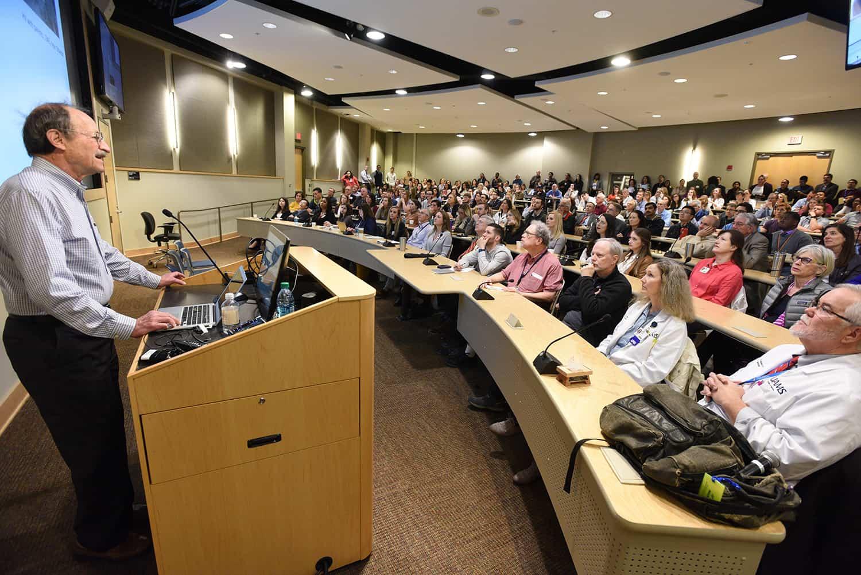 Scientist at podium addressing large crowd