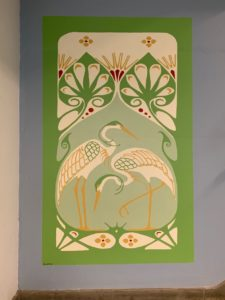 Merideth Addicott, an assistant professor in the Psychiatric Research Institute, recreated a green art nouveau-style mural of two herons by A. Smit.