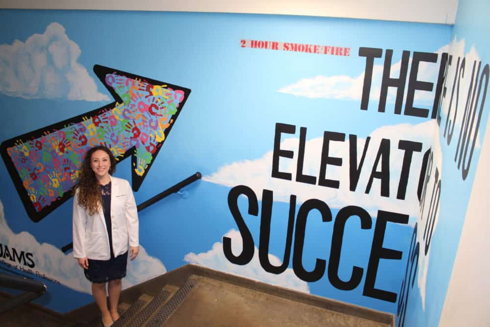Marissa Miller, a student in the Physician Assistant Studies program, stands beside her mural.