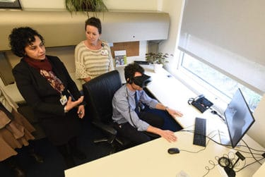 Mendiratta, left, and Marcia Byers watch King as he begins using a virtual reality simulation.
