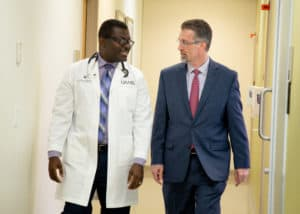 Mark Bremer talks with colorectal surgeon Jonathan Laryea, M.D. in a UAMS clinic.