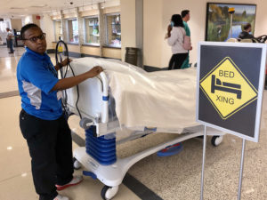 Chelsey Harris pauses next to a bed crossing sign as she transports a bed from the loading dock to a patient room.