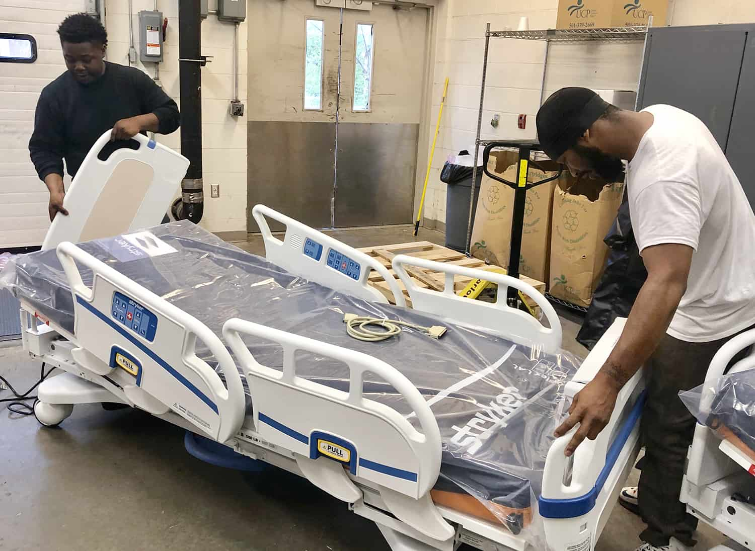 Jalen Morris (left) and Bradon Berry, contract employees with Stryker, assemble new patient beds in the UAMS loading dock. More than 300 patient received new beds in April.