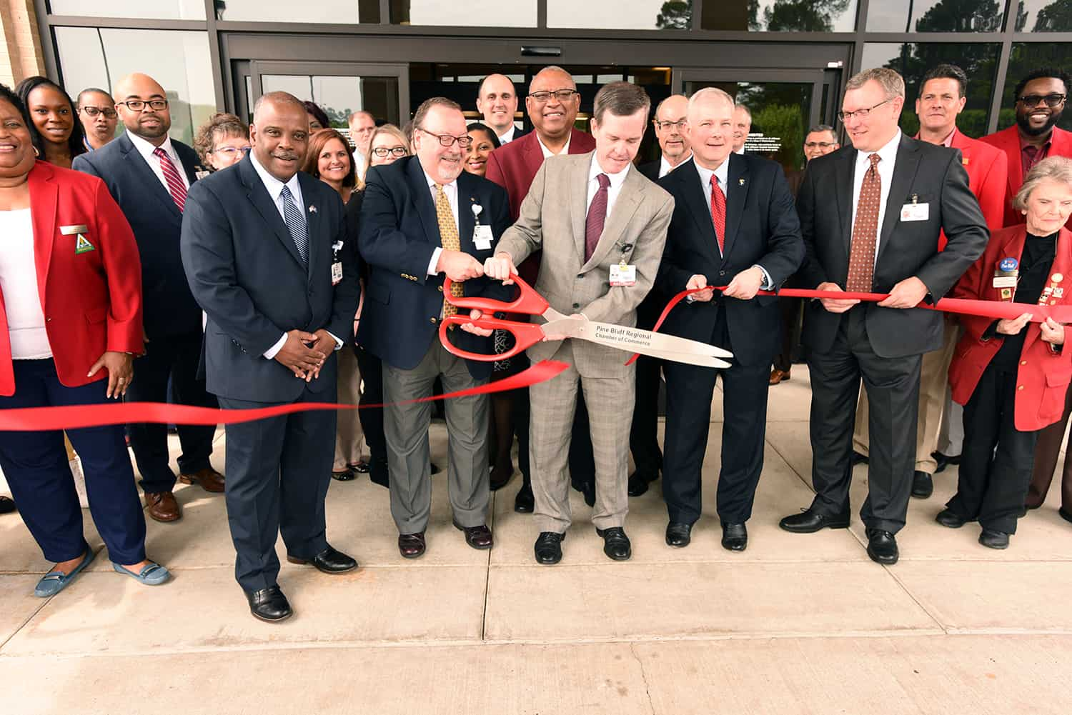 Mark Deal and Chancellor Cam Patterson use oversized scissors from the Pine Bluff Regional Chamber of Commerce for the official ribbon cutting at the South Central Regional Campus.