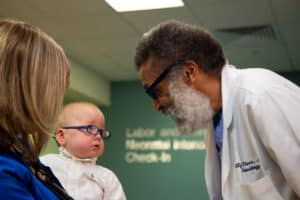 Neonatologist Billy Thomas, M.D. shows Hayes his own pair of blue-framed glasses.