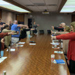 Employees from the UAMS Office of Communications and Marketing stretch during a team meeting.