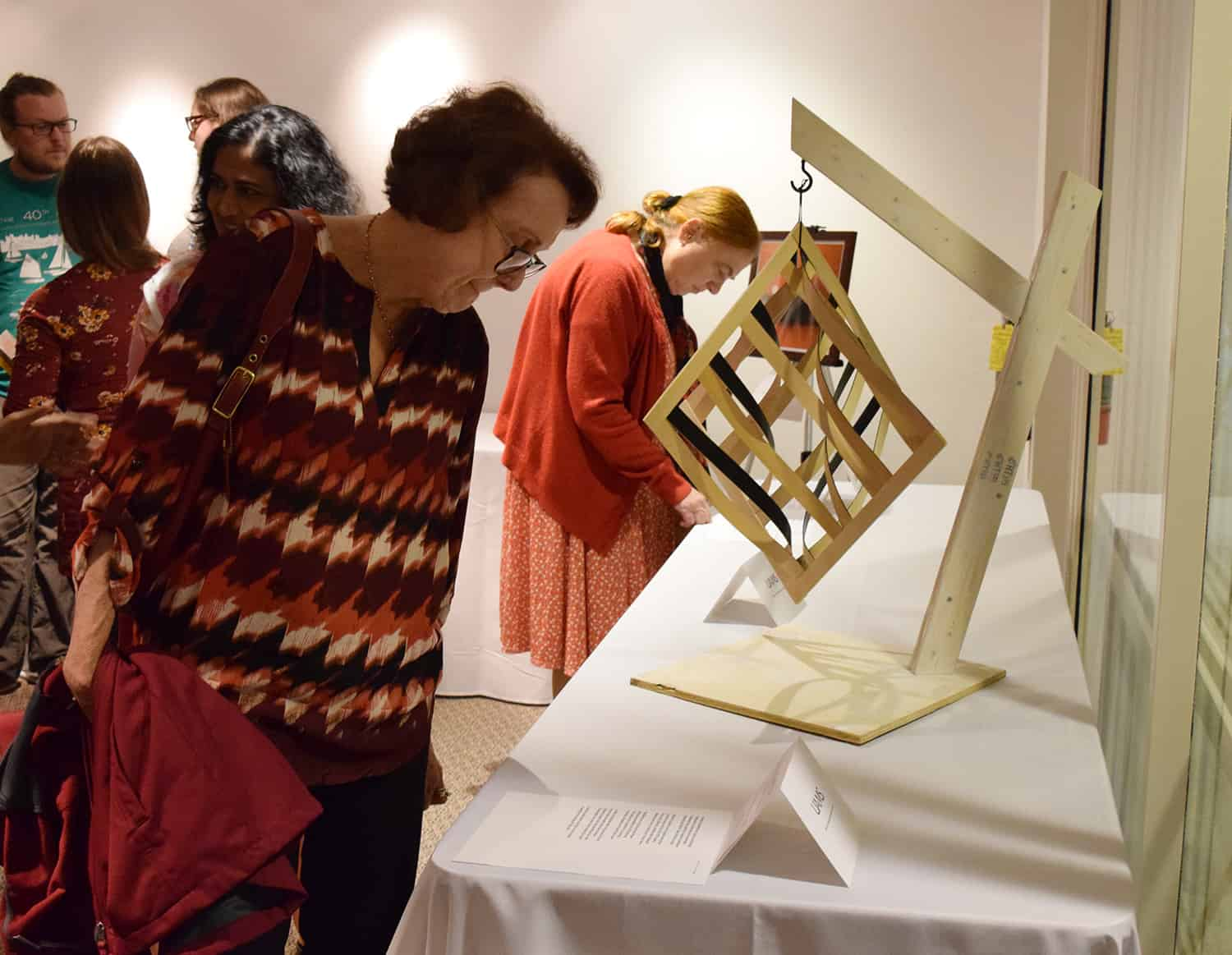 An Art from the Heart attendee examines Octahedral with Curve, a woodwork piece created by Shalese Fitzgerald.