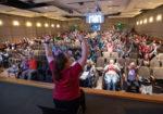Demonstrator leading audience in chair yoga