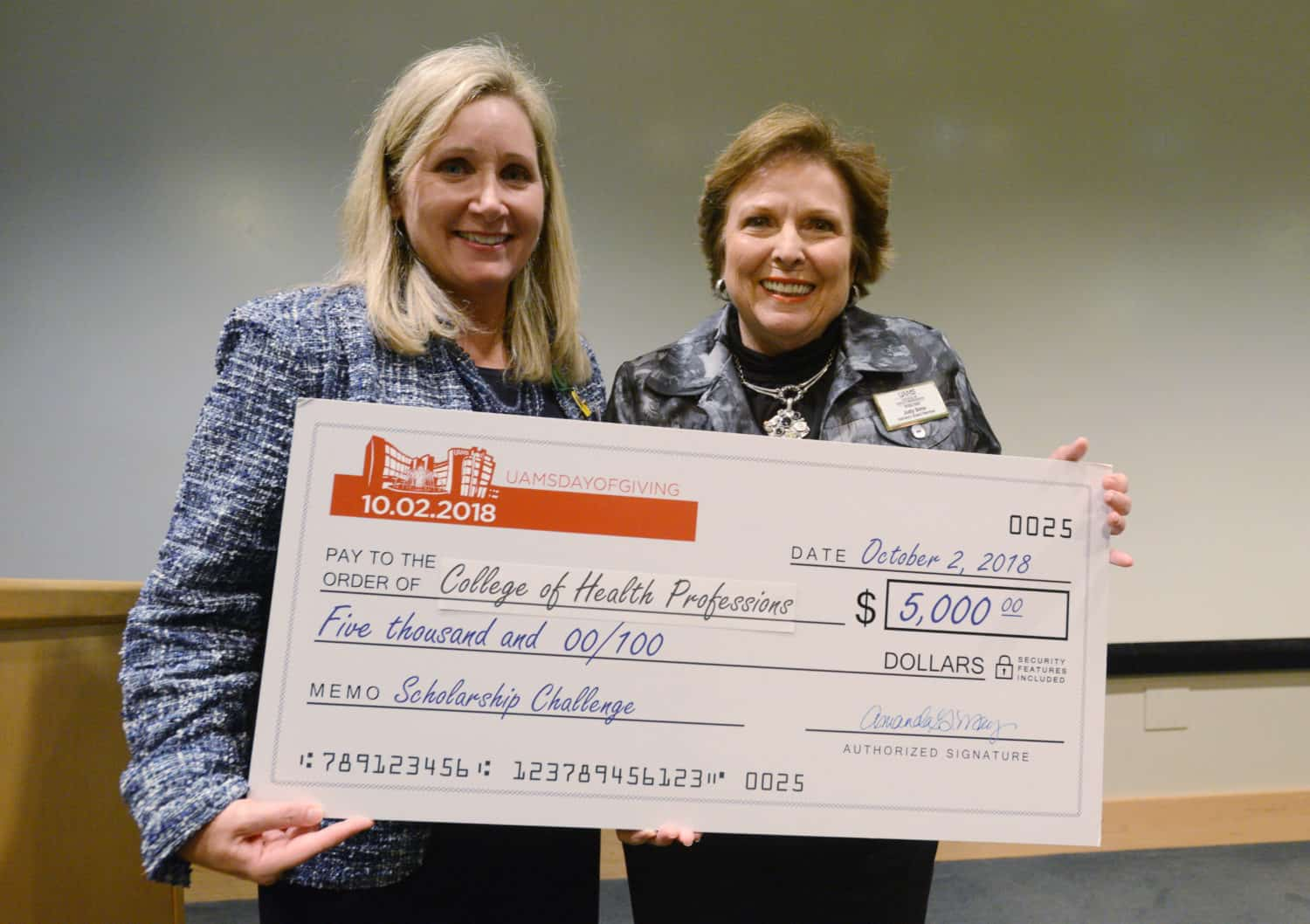 College of Health Professions Dean Susan Long, Ed.D., (left) accepts a check from Judy Sims, the then-chair of the college's Advisory Board, during a scholarship program in November.