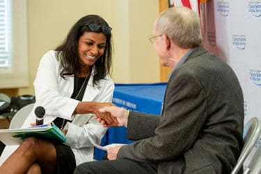 Masil George, M.D., left, shakes hands with a volunteer at the end of a roleplay exercise demonstrating how to talk to patients and older adults about their opioid use.