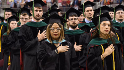 Sharanda Williams (center), director of Academic Affairs in the UAMS College of Medicine, stands as marshal with students ready to receive their diplomas.
