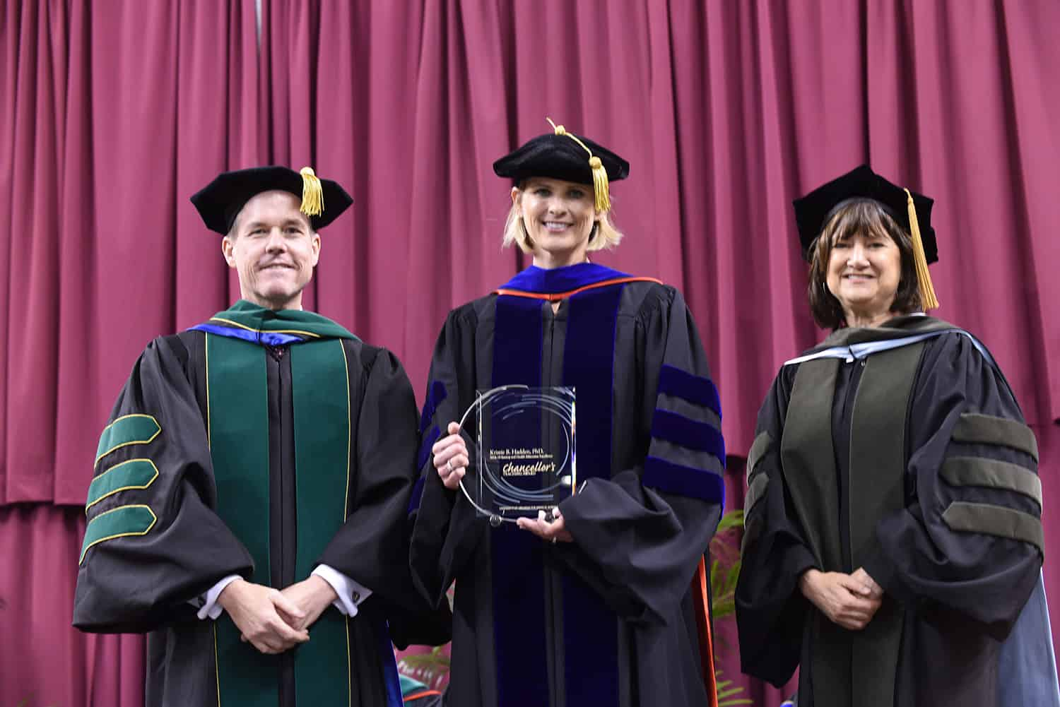 UAMS Chancellor Cam Patterson, M.D., MBA, and Provost Stephanie Gardner, Pharm.D, Ed.D., present Kristie Hadden, Ph.D., (center) with the Chancellor's Award for Society and Health Education Excellence.