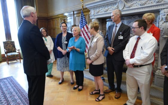 Betty Fortner, a cancer survivor and clinical trial participant, briefly told her story to Gov. Asa Hutchinson and UAMS and ACRI research leaders during a photo opportunity for Clinical Trials Day.