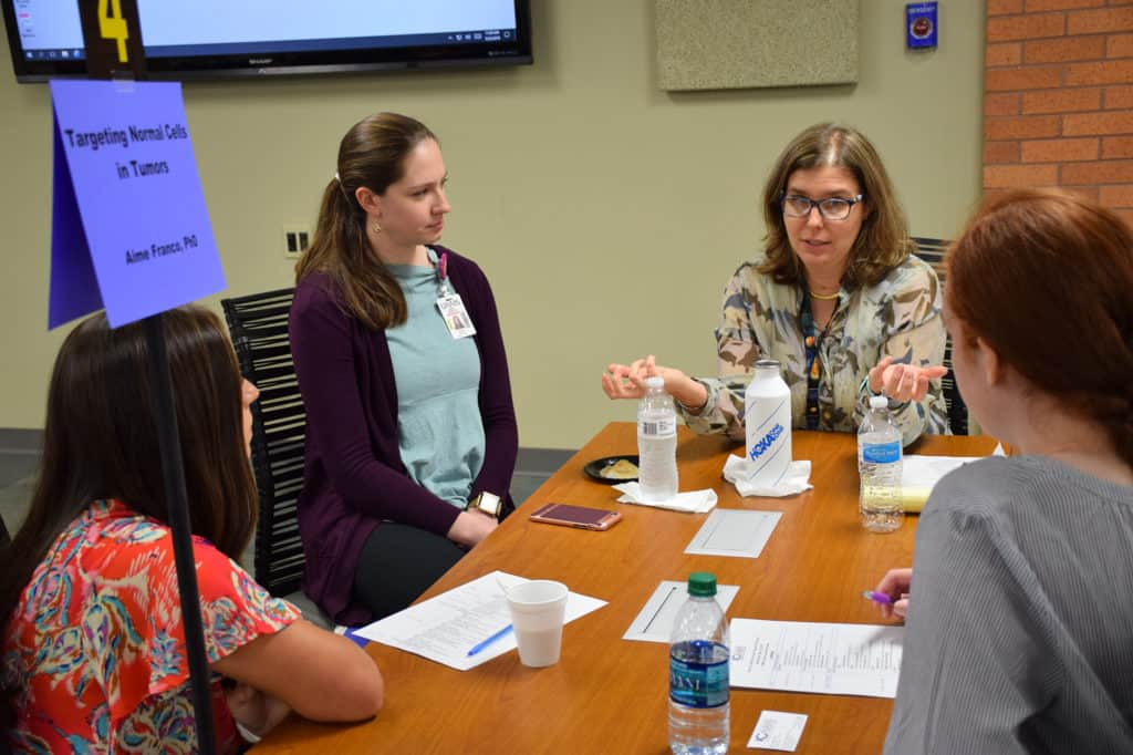 Participants engage in a small-group discussion with thyroid cancer researcher Aime Franco, Ph.D.