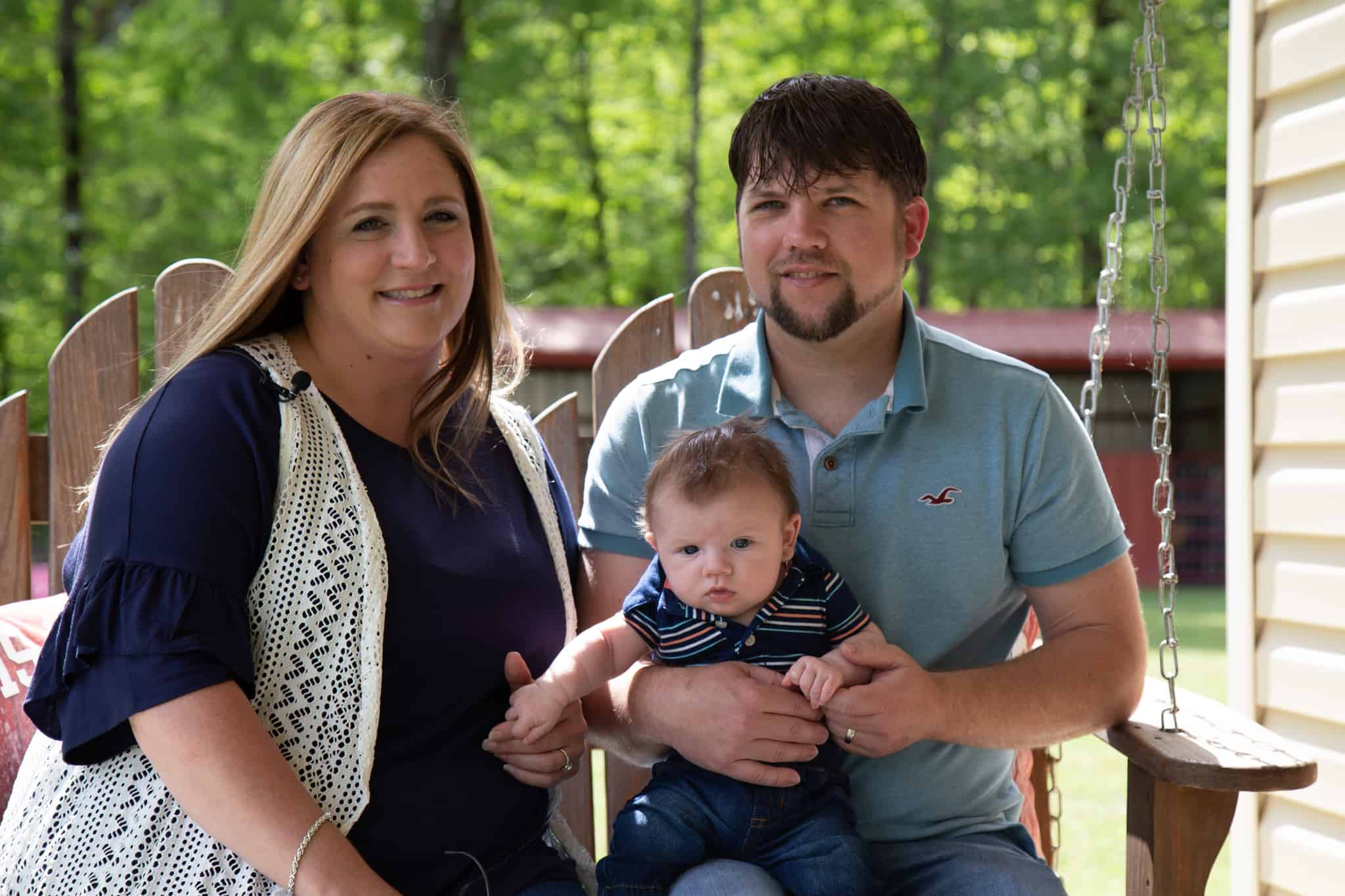 Laci, Cole and Rickie Bratton sit on a porch swing at their Monticello home.