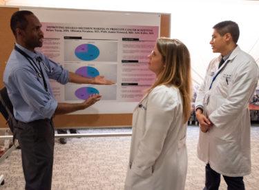 Doctors talking near poster
