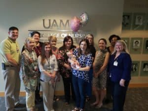 Sarah Guarnieri (center) holding her new infant and surrounded by College of Nursing faculty following her pinning.